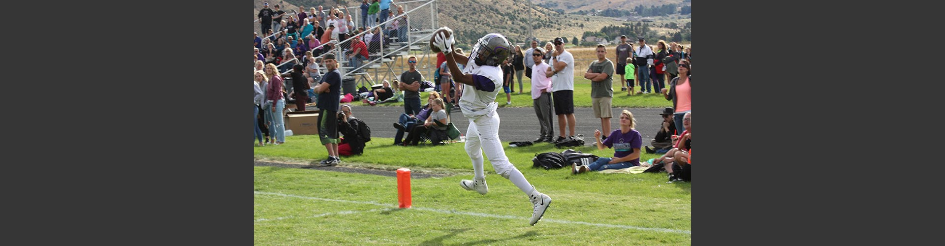 Student athlete catching football during a football game.